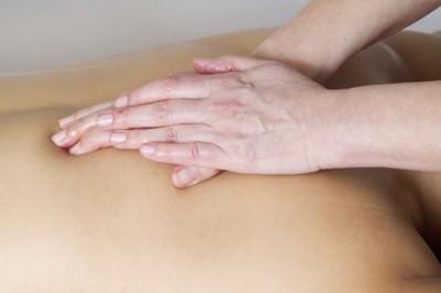 Personne qui pratique un massage sur un dos.