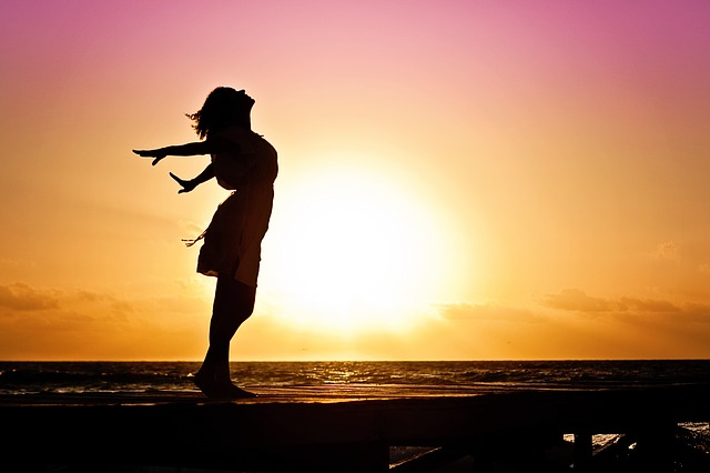 Femme libre devant un coucher de soleil.