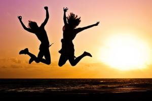 Deux personnes sautant de joie devant le soleil couchant.