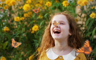 Laughing curly girl with a butterfly on his nose. Healthy smile with white teeth. Free breathing concept.